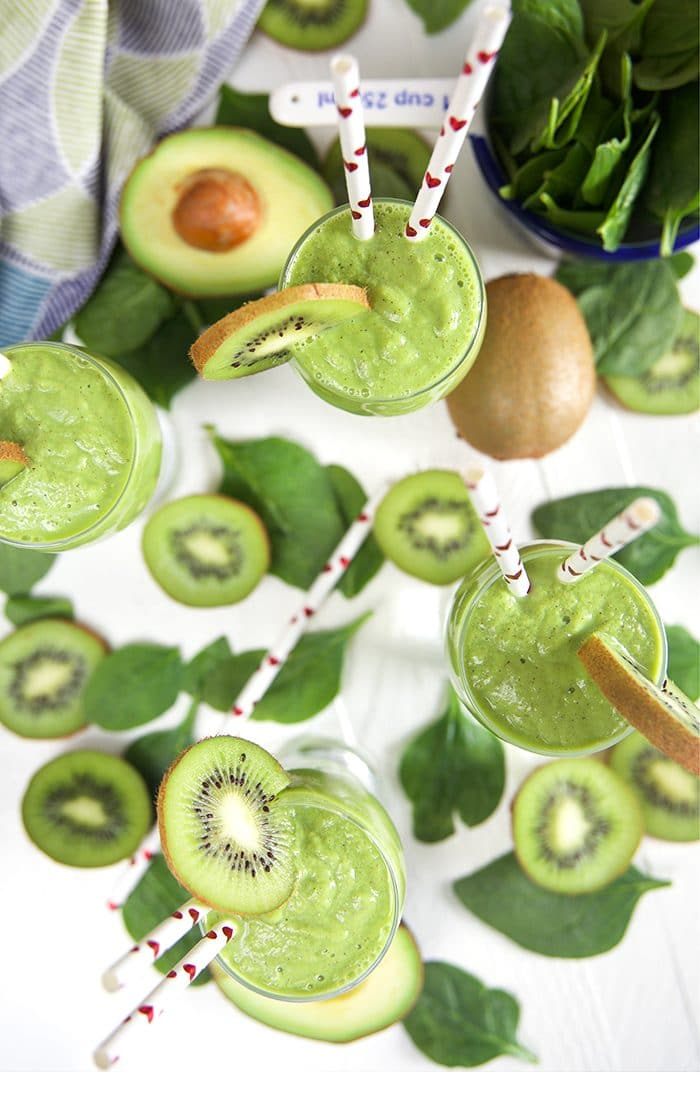 Overhead shot of three Kiwi Pineapple Spinach Smoothies on a white background with kiwi slices and spinach leaves around.