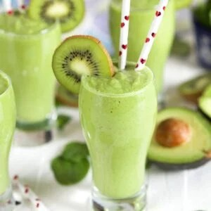 Kiwi Pineapple Spinach Smoothie in a small pilsner glass with a kiwi on the rim and two straws with red hearts.