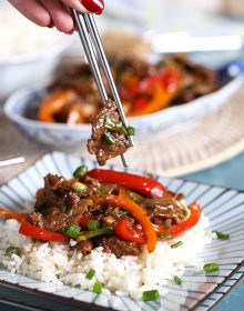 Mongolian Beef on a bed of white rice with a bite in silver chopsticks.