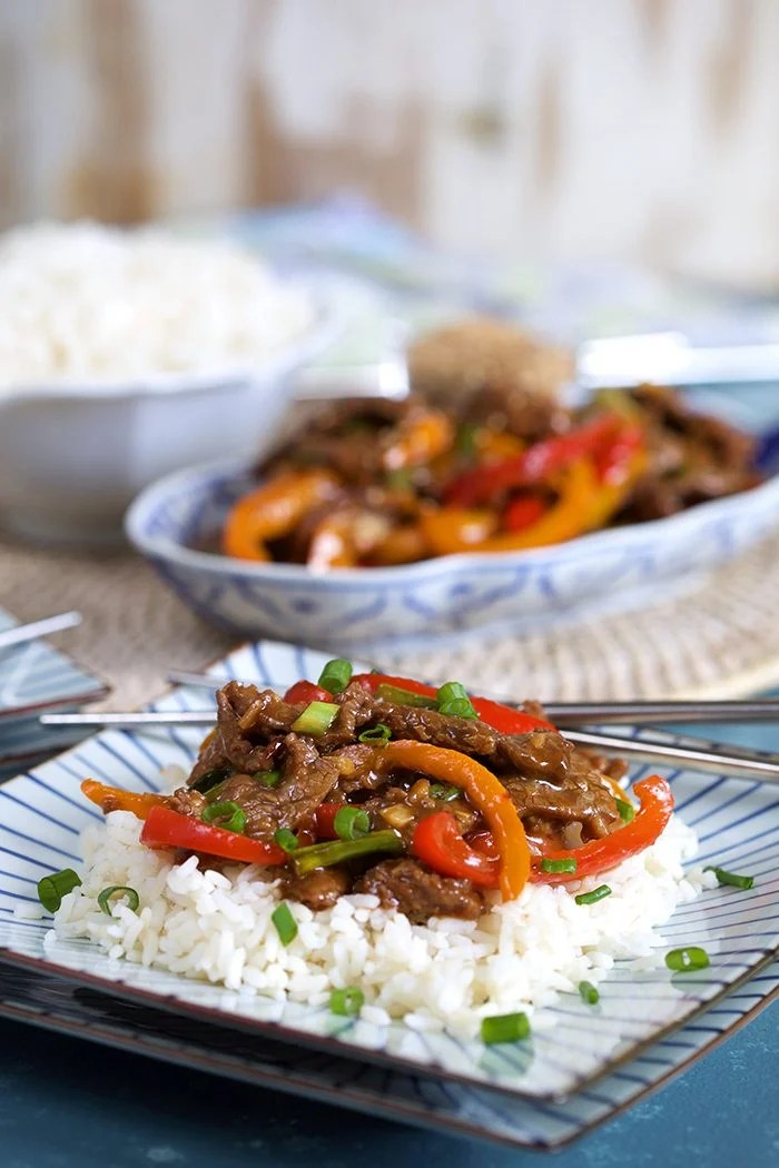 Mongolian Beef Stir Fry on a bed of white rice on a square blue and white plate with silver chopsticks.