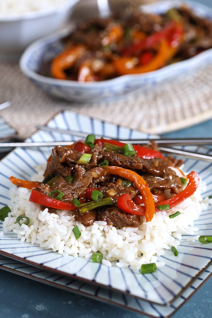 Mongolian Beef Stir Fry on a bed of white rice on a blue and white square plate.