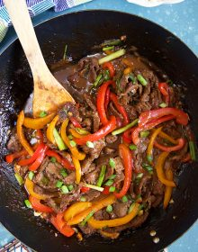 Overhead shot of Mongolian Beef Stir Fry in a wok with a wooden spatula.
