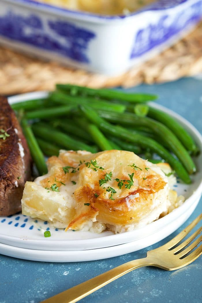 Easy Scalloped Potatoes on a white plate with green beans and filet mignon.