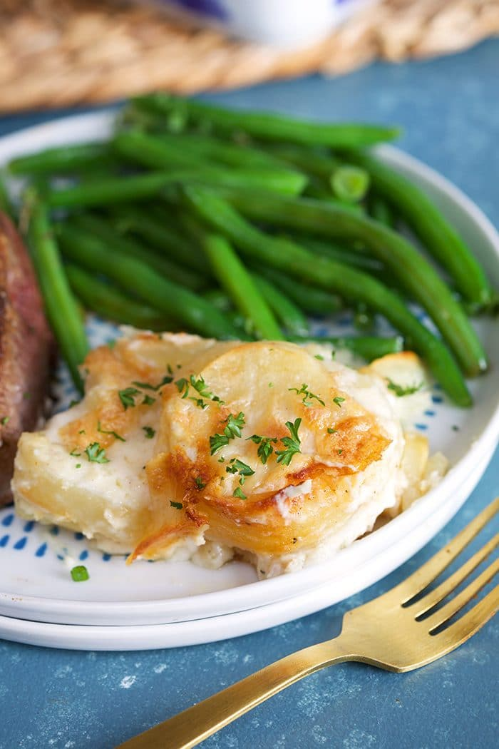 Close up of homemade scalloped potatoes on a white plate with green beans and a gold fork on a blue background.