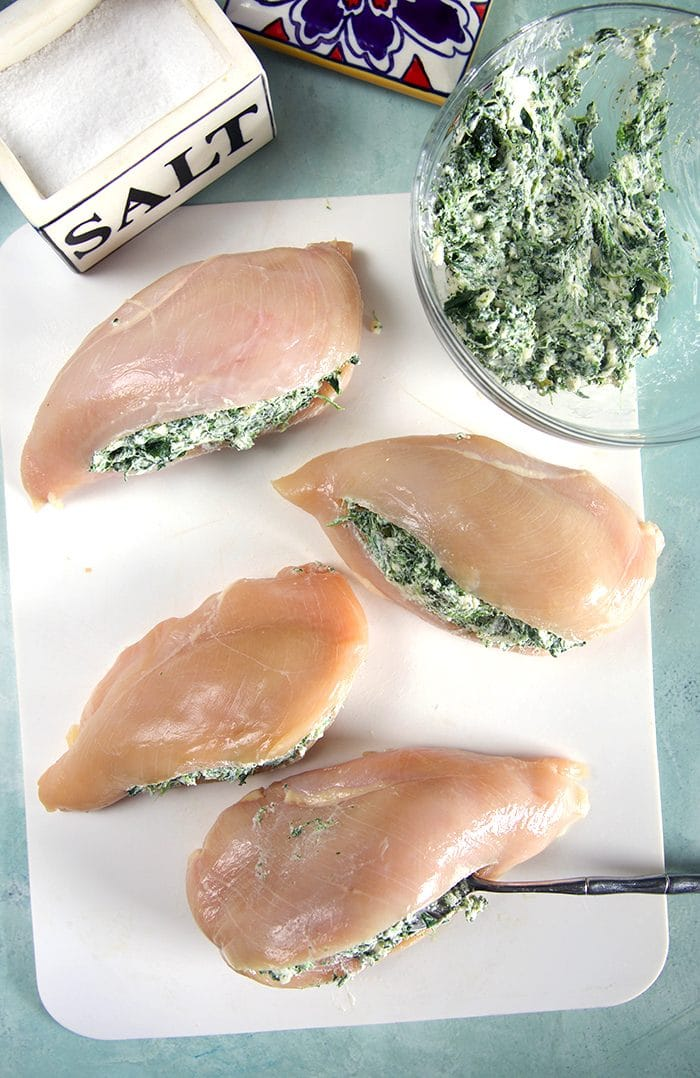 Overhead shot of four raw chicken breasts with spinach dip stuffing and a salt box on a white cutting board.