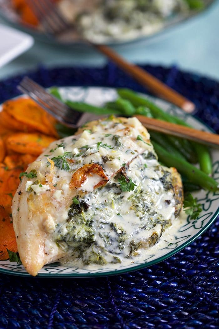 Close up of Cheesy Spinach Stuffed Chicken Breast on a plate with green beans and roasted carrot slices.