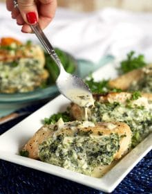 Spinach and cheese stuffed chicken breasts with a spoonful of garlic parmesan sauce drizzled overtop.