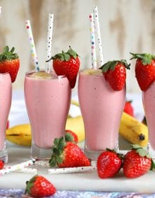 Four Strawberry Banana Smoothies in pilsner glasses with paper strawberry and a strawberry on the side.