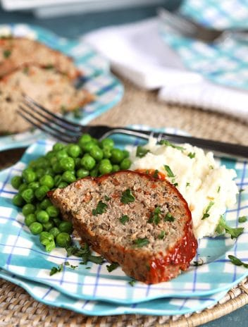 Slice of turkey meatloaf on a blue plaid plate with mashed potatoes and peas.