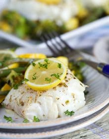 Lemon Baked Cod Loin on a white plate with vegetables.