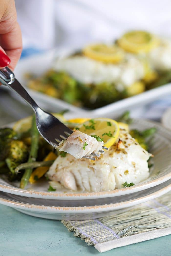 A fork with a bite of lemon baked cod on a white plate with green vegetables.