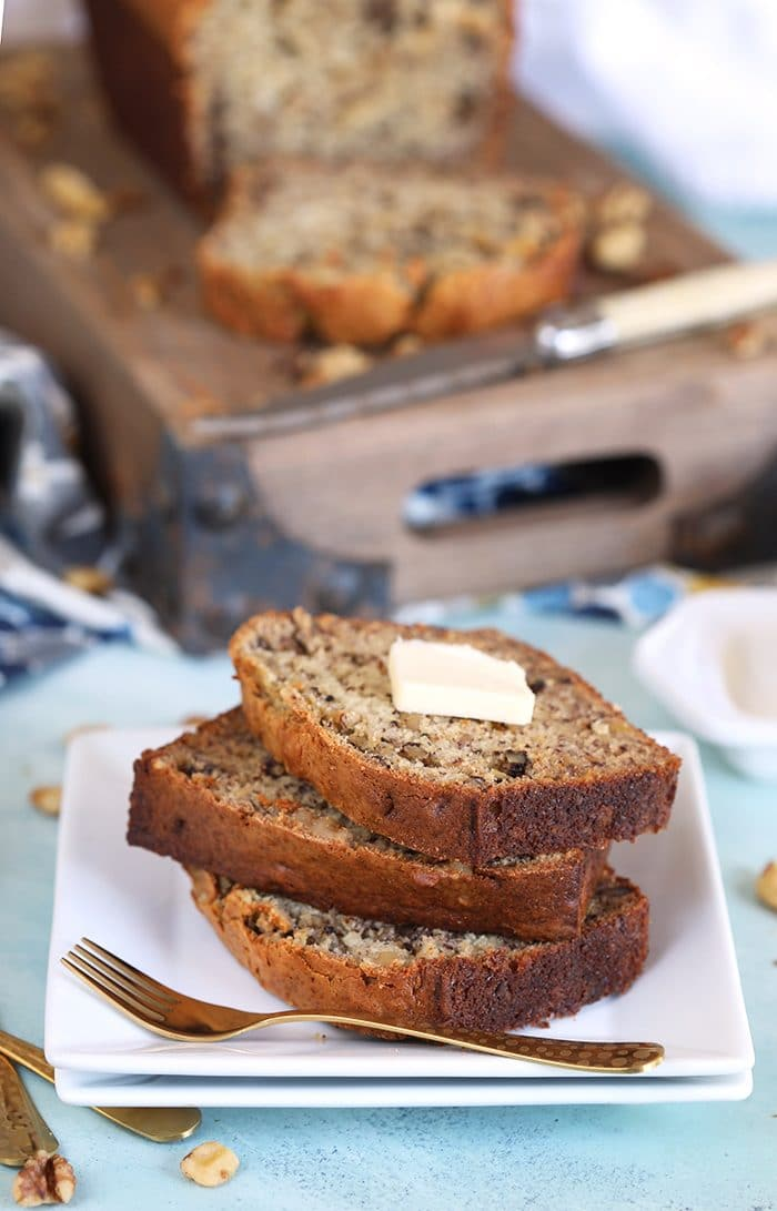 Three sliced of banana nut bread with a pat of butter on top on a white square plate with a gold fork.