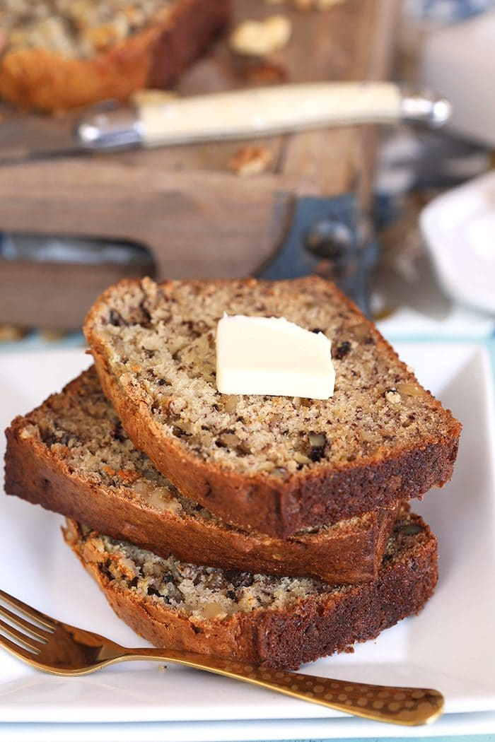 Three slices of Banana Nut Bread stacked on a white square plate.