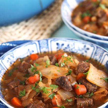 Sweet and Sour Beef Cabbage Soup recipe in a blue and white bowl.