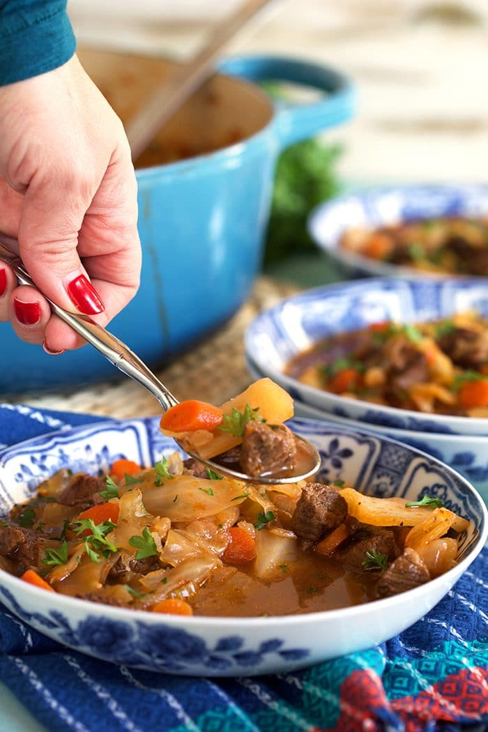 Beef Cabbage Soup recipe in a blue and white bowl with a spoonful above the bowl.