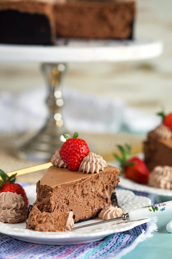 Slice of Chocolate Cheesecake on a white plate with a strawberry on top.