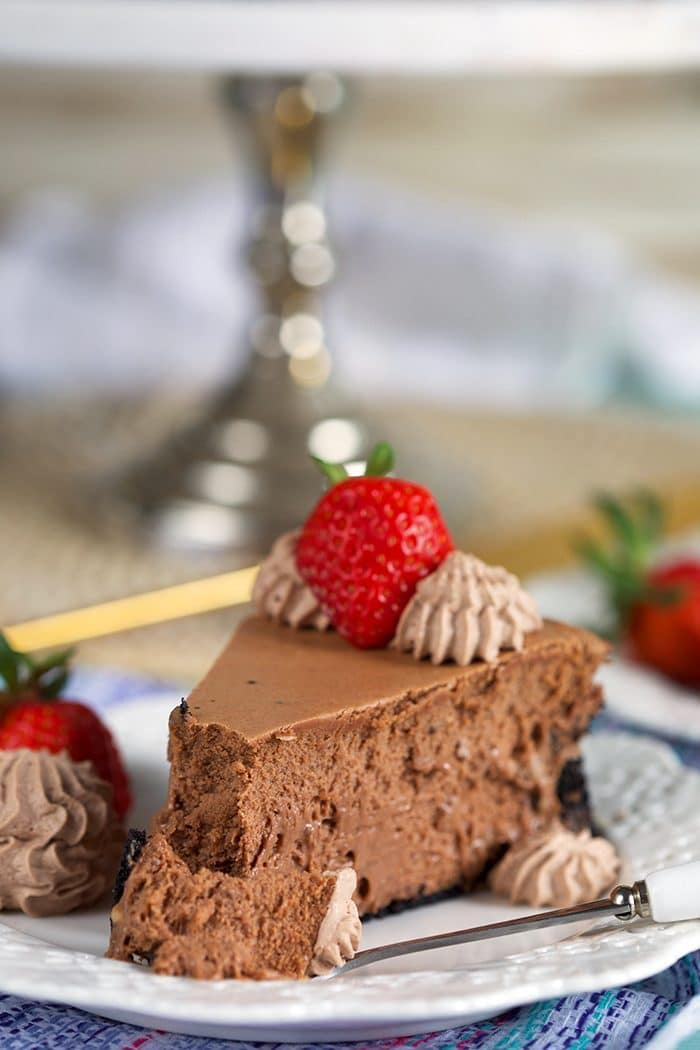 Slice of Chocolate Cheesecake with a strawberry on top and bite on a fork.