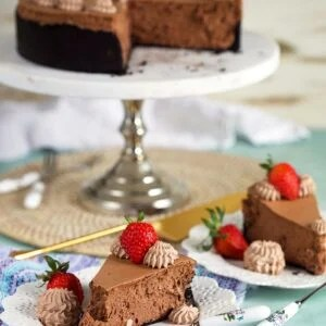Two slices of chocolate cheesecake on white plates with a whole chocolate cheesecake on a marble cake plate in the background.