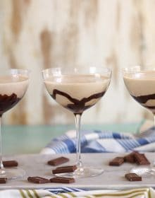Three chocolate martinis lined in a row on a marble platter.