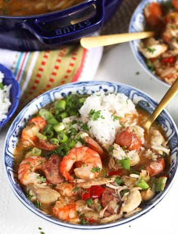 Overhead shot of seafood gumbo with a pile of rice in a blue and white bowl on a white background.