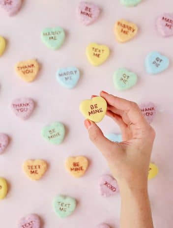 Valentine Conversation Heart Bath Bombs with a hand holding a yellow heart against a pink background.