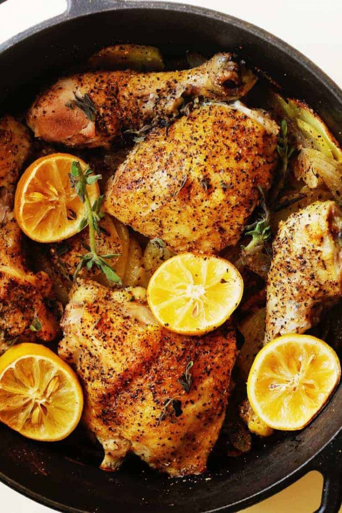Baked Chicken with lemons in a cast iron skillet.