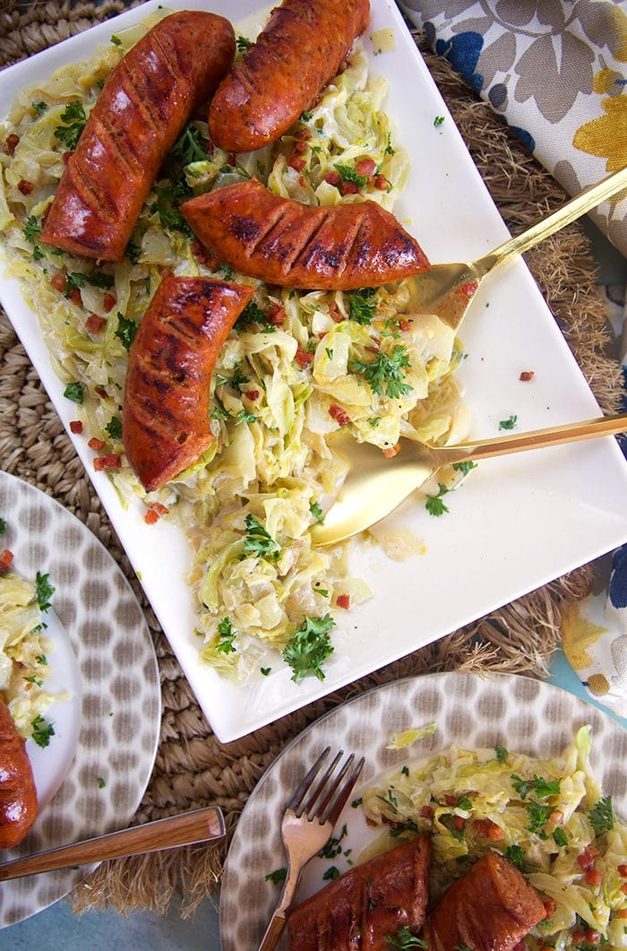 Overhead shot of fried cabbage and kielbasa on a white platter with a gold serving spoon.