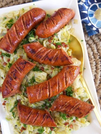 Overhead shot of kielbasa on a bed of fried cabbage on a white rectangular platter.