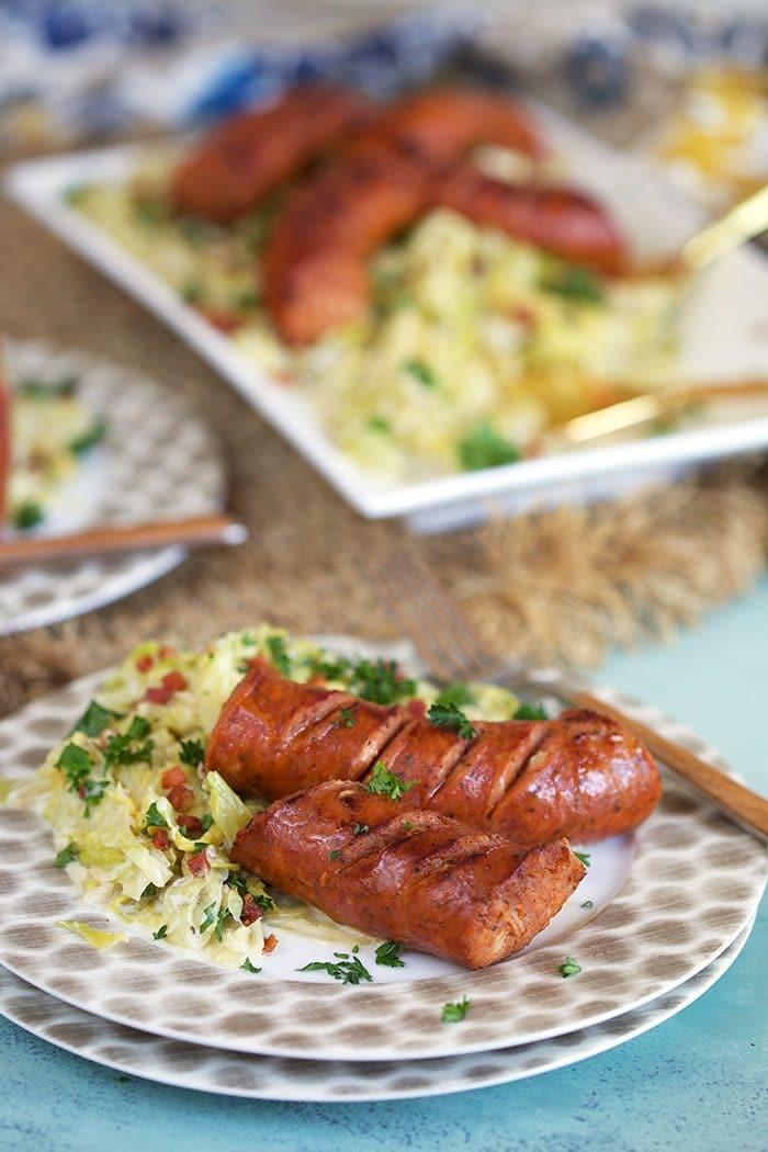 Fried Kielbasa on a white plate with fried cabbage and a platter with cabbage and kielbasa in the background.