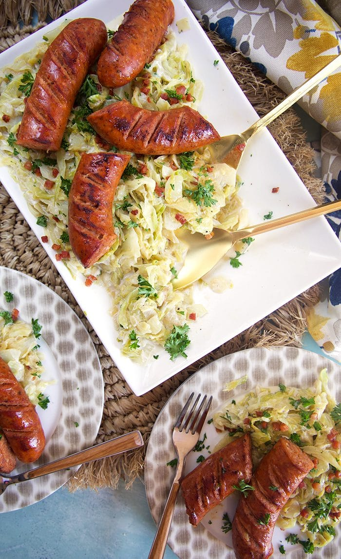 Overhead shot of fried cabbage and kielbasa on a white platter.