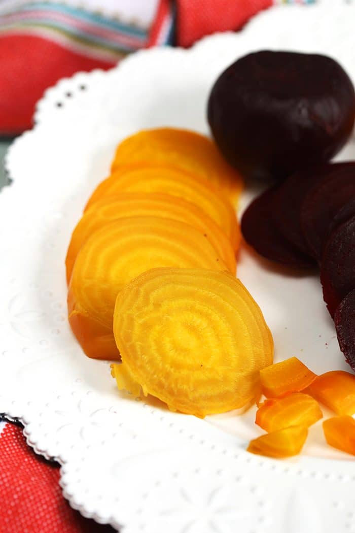 Golden and red cooked beets on a white plate.