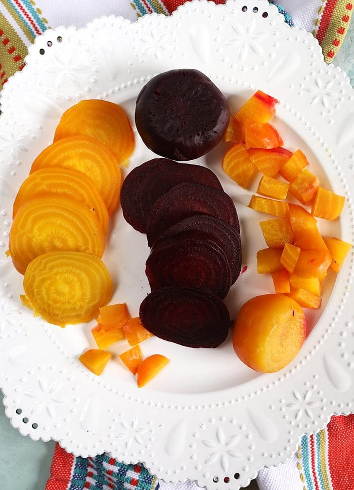 overhead shot of golden and red cooked beets on a white plate.