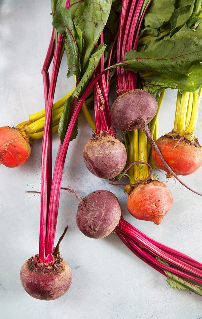Pile of beets on a blue background.