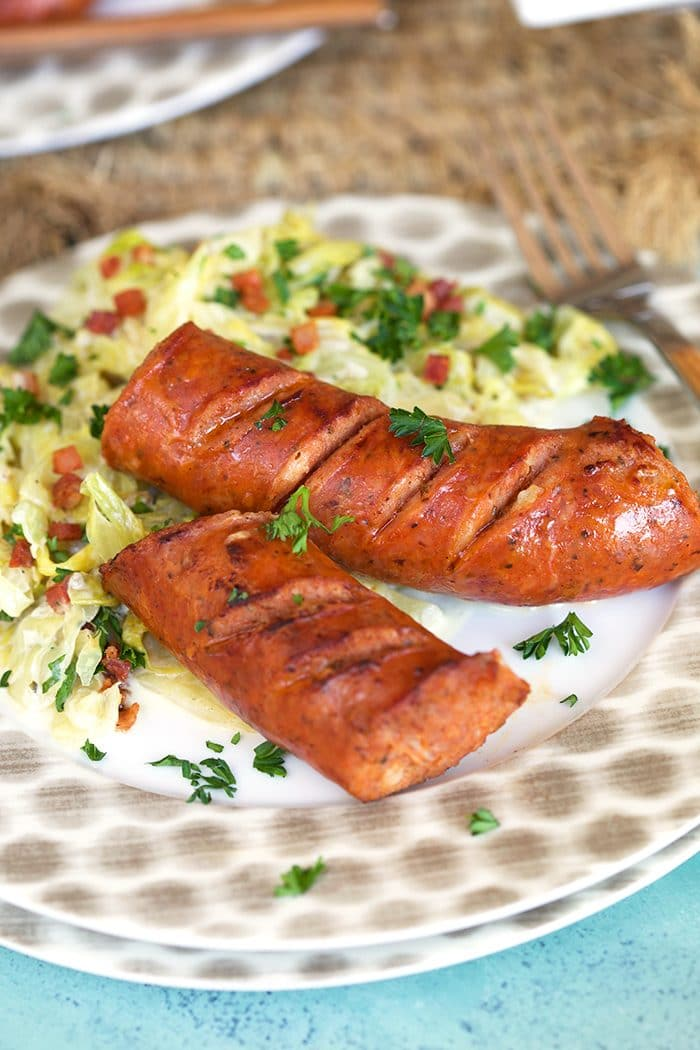 Fried Kielbasa with cabbage on a white plate.