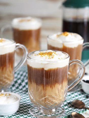 Nutty Irishman in a glass coffee mug with whipped cream and gold sprinkles on a green and white checked napkin.