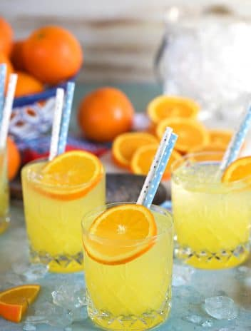Three orange crush cocktails on a blue background with an ice bucket.