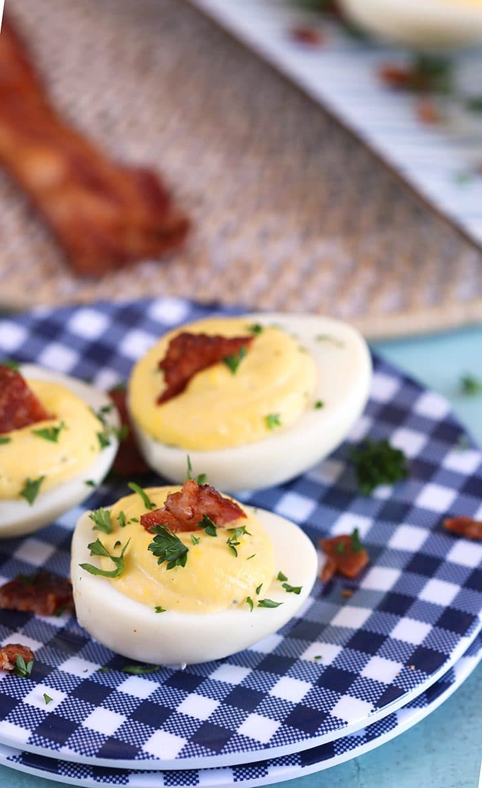 Bacon Horseradish Deviled Eggs on a blue and white gingham plate with bacon in the background.
