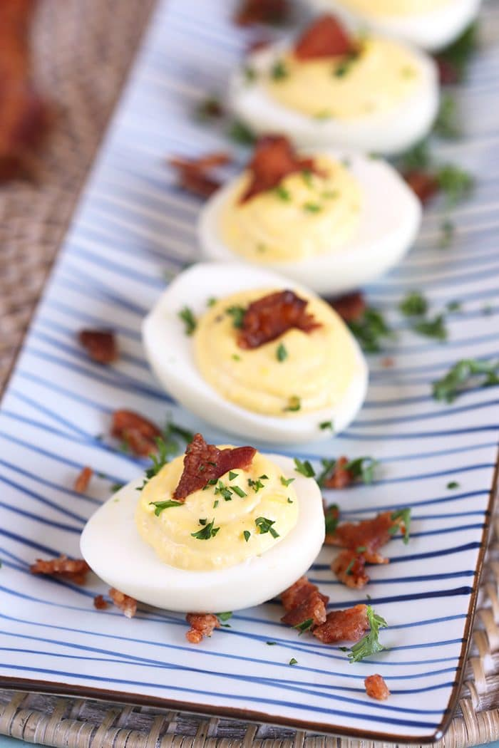 Overhead shot of bacon horseradish deviled eggs on a blue and white striped platter.