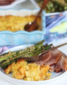 Baked Pineapple Casserole on a white plate with ham and asparagus.