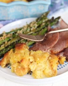 Baked pineapple on a white plate with ham and asparagus.