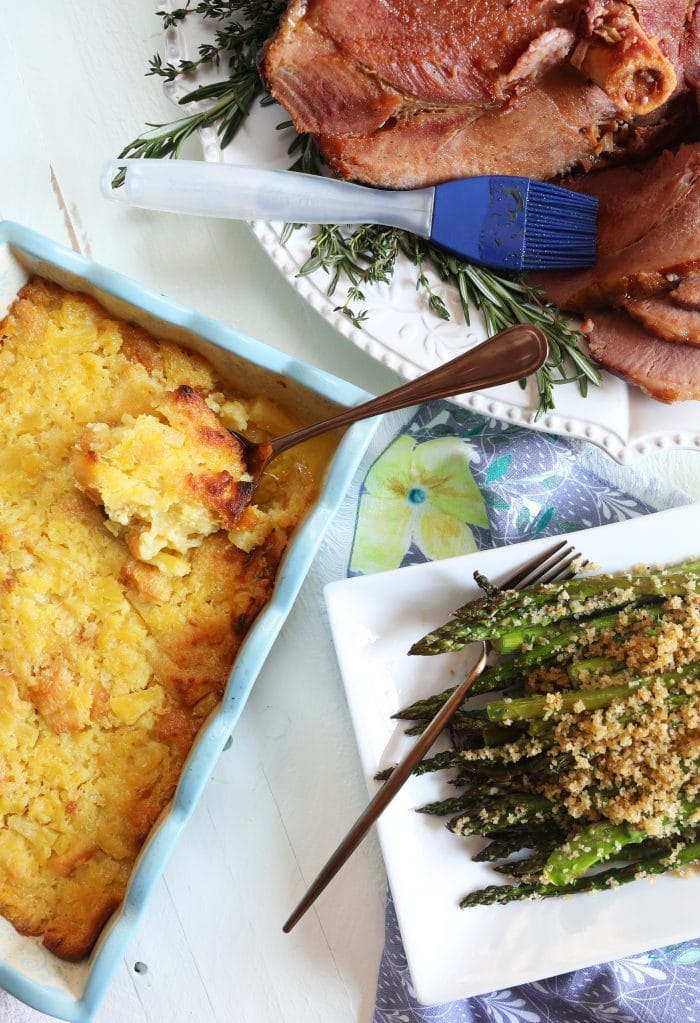 Overhead shot of Baked Pineapple Casserole with a platter of asparagus and a baked ham.