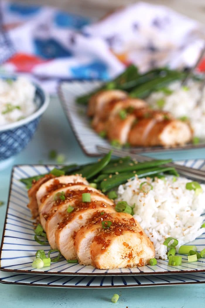 Sliced Teriyaki Chicken breast on a plate with rice and green beans.