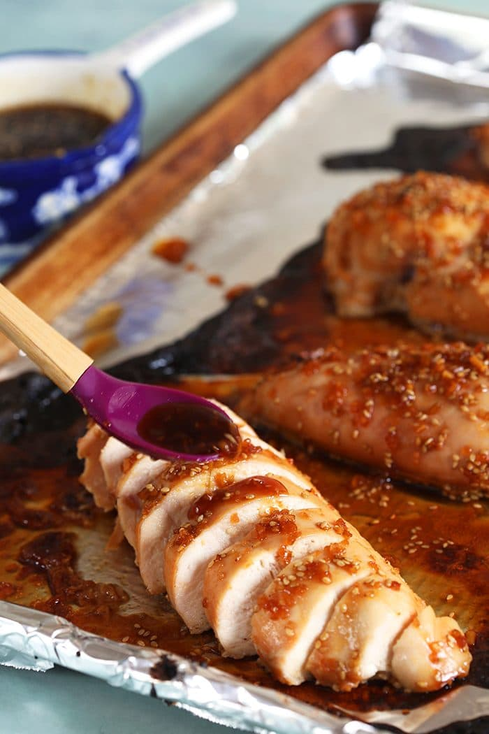 Sliced Teriyaki Chicken on a baking sheet with a spoon drizzling sauce over the chicken.