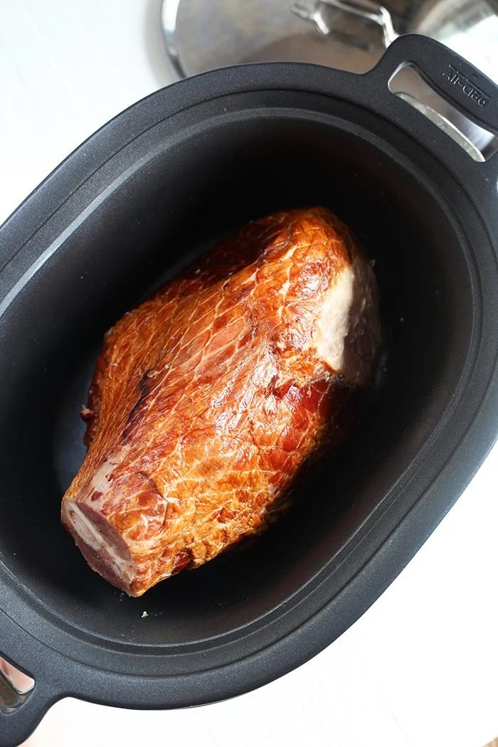 Overhead shot of ham in a slow cooker.