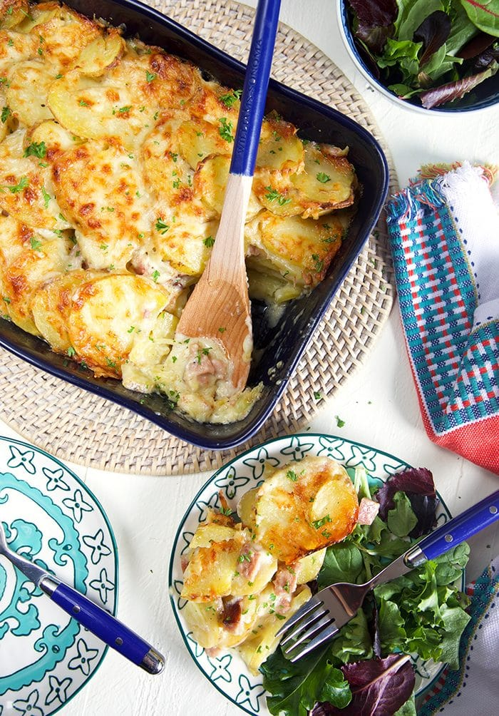 Overhead shot of scalloped potatoes with ham casserole recipe in a blue casserole dish.