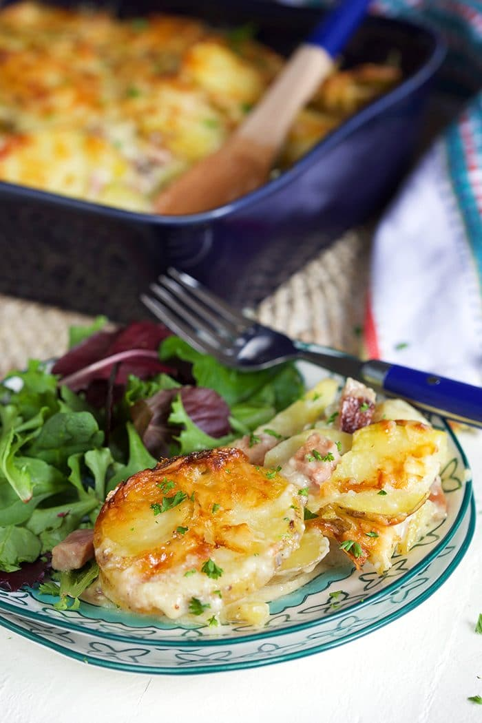 Easy Scalloped Potatoes with ham on a blue and white plate with a green salad.