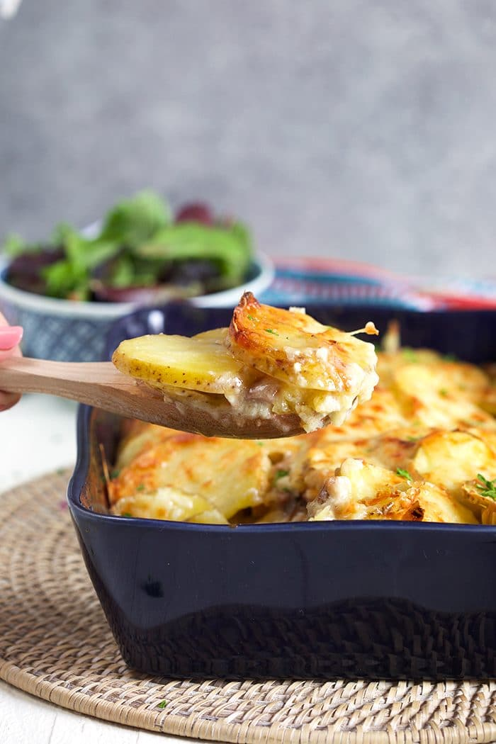 Ham and Scalloped Potatoes in a blue casserole with a wooden spoon scooping out a serving.