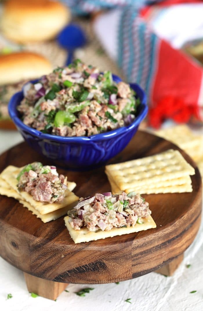 Ham salad on a Town cracker with a bowl of ham salad in a blue bowl.