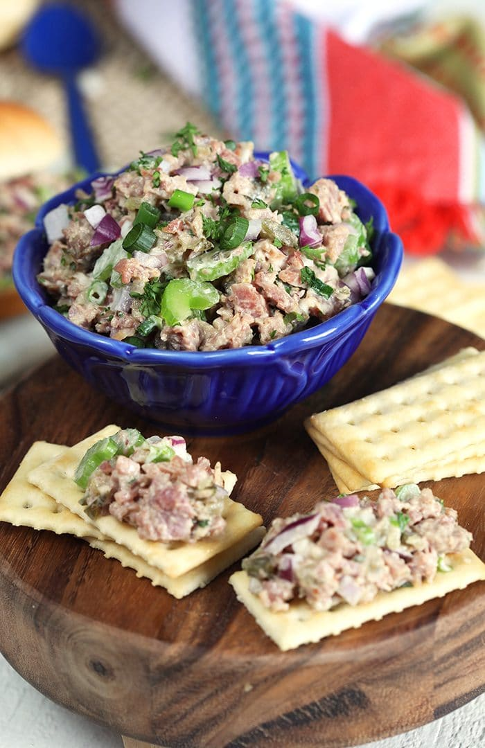 Ham Salad in a blue bowl on a wooden board with crackers.