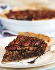 Close up of pecan pie on a white plate.